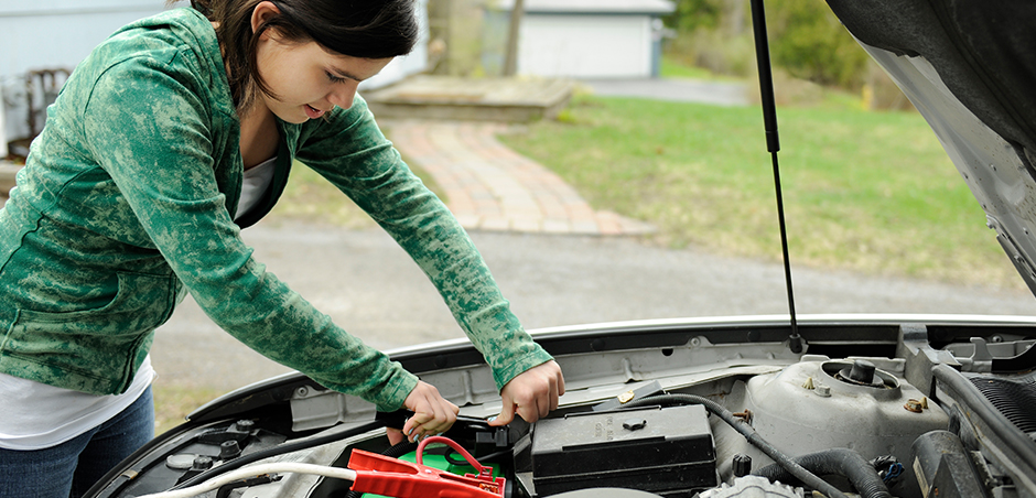 woman opens car hood to work on engine
