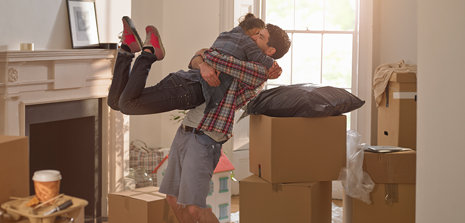 man embraces and lifts woman while unpacking moving boxes in living room