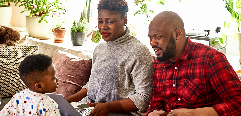 woman and man sit on couch with laptop while small child looks on