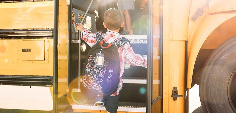 young boy boards a school bus