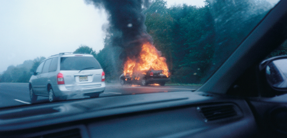 Car is on fire on the side of the road, while a silver minivan passes to the left.