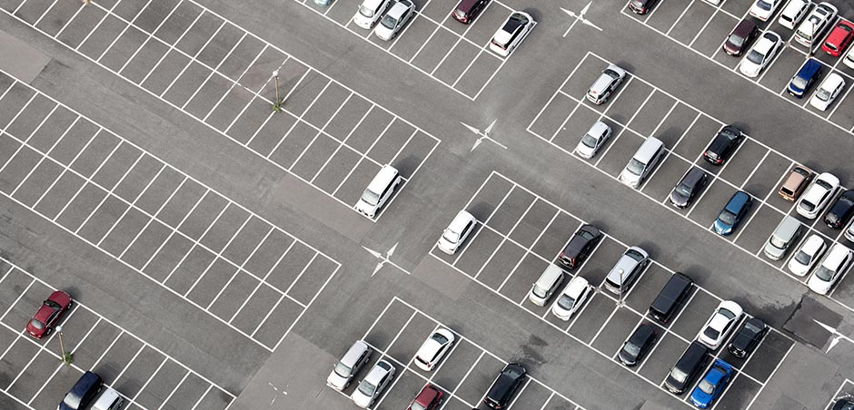 aerial view of vehicles in large parking lot, with most spaces left empty