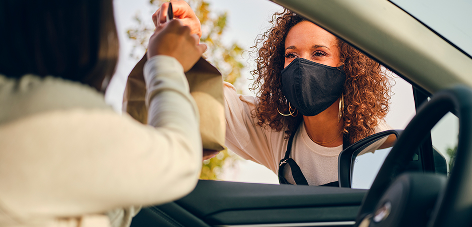 woman wearing mask hands brown paper bag to person in driver's seat of car