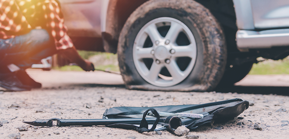 medium shot of flat tire on a car; equipment in the foreground and person kneeling next to tire in background