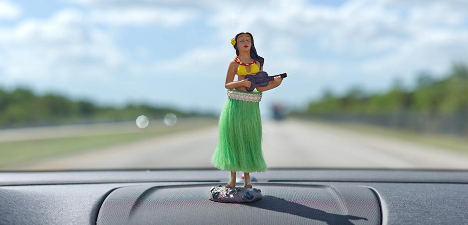 close up of hula dancer figurine on car dashboard