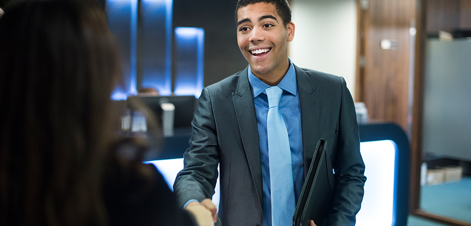 young man in business suit shakes hands with person out of frame