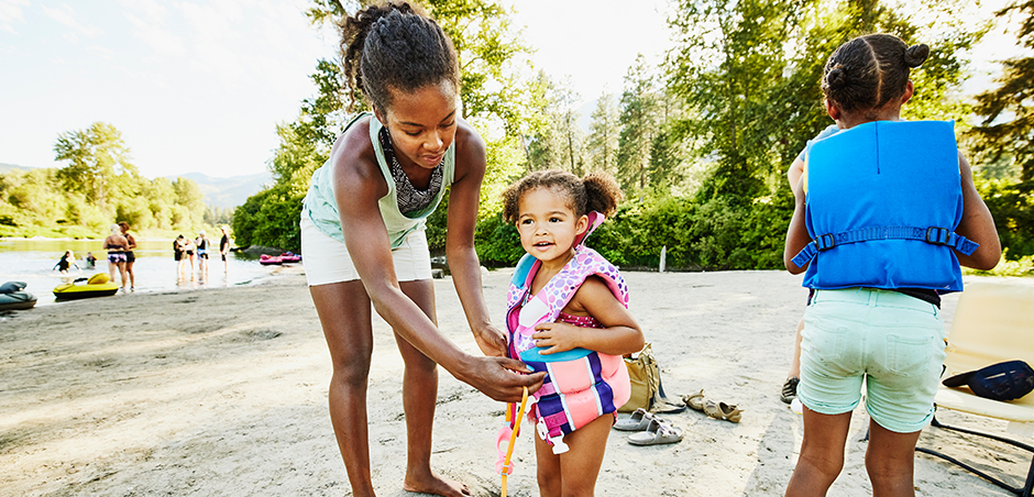 mother assists young daughter in putting on her life jacket, while older child looks ahead.