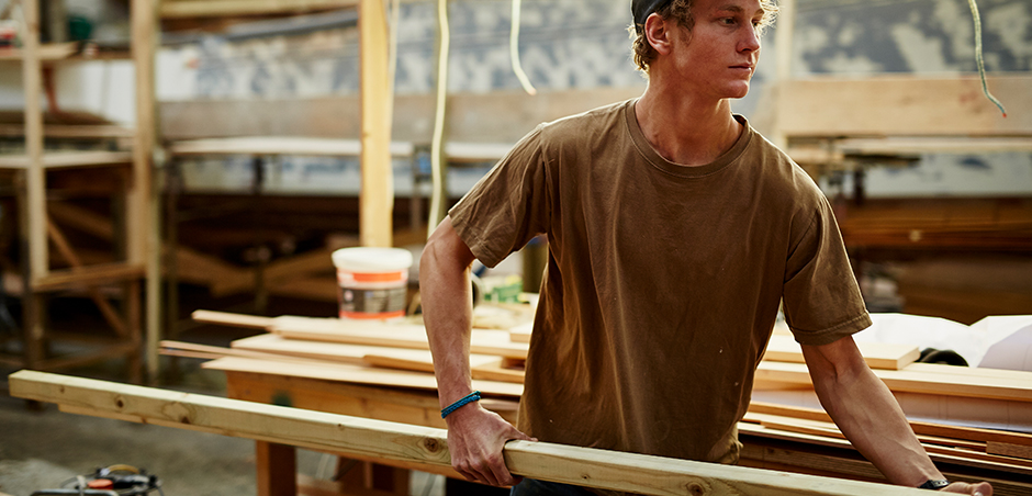 young man carries board in a lumber yard