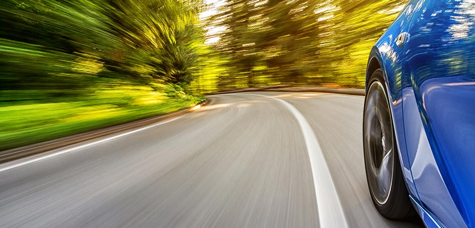 medium shot of front driver's side wheel of a car with motion blur around road, indicating fast driving