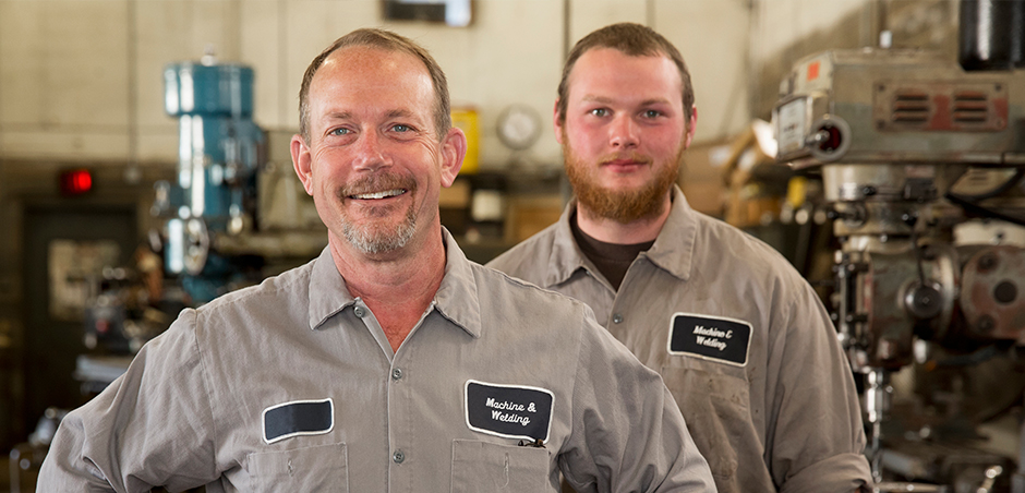 In a machine shop, a middle aged man stands in front of a young adult man. Both are wearing work shirts with nametags.