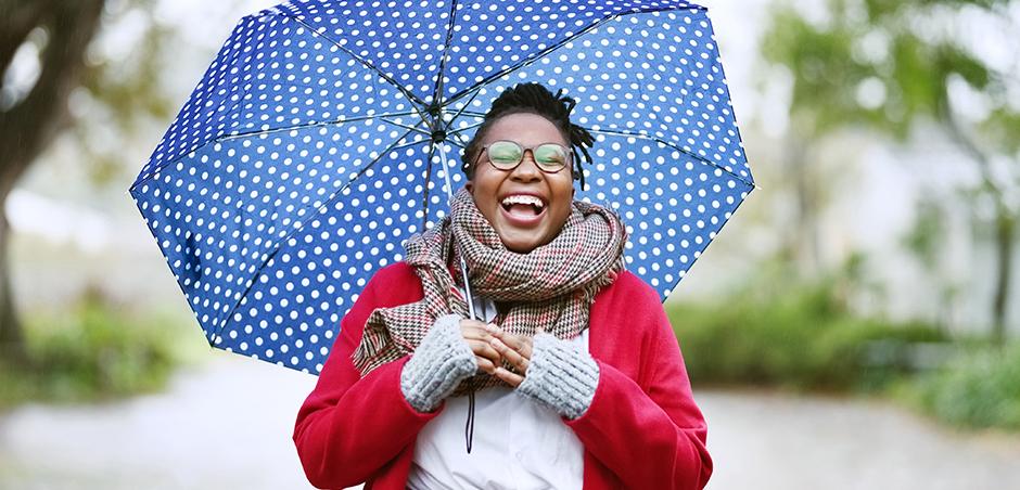 smiling woman holds polka dot umbrella outside