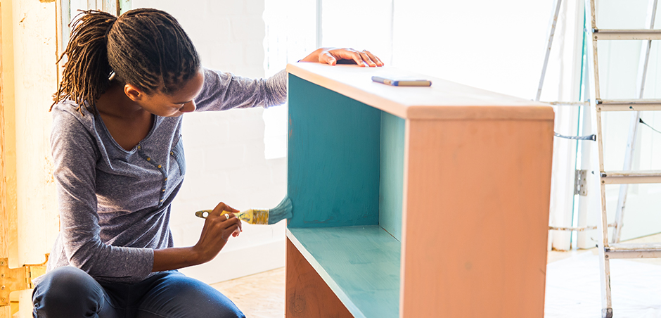woman paints bookcase