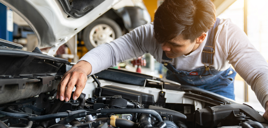mechanic opens hood of car and examines engine