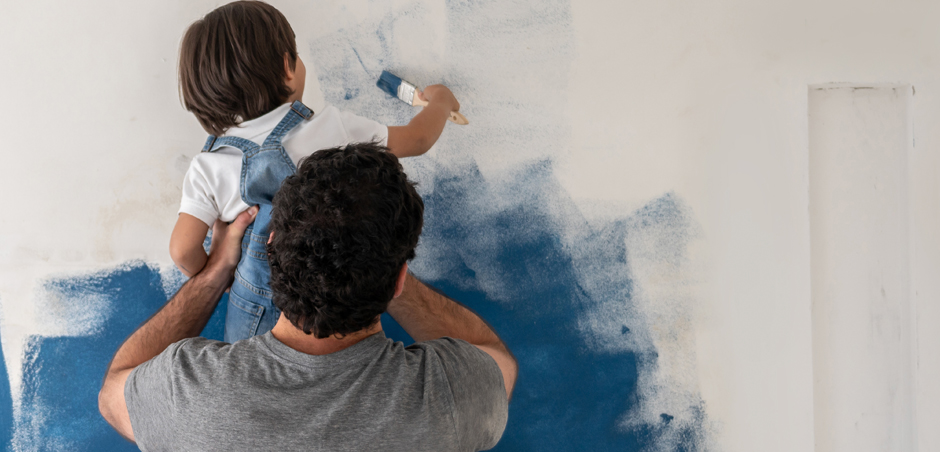 young child, held up by adult man, brushes blue paint on interior house wall