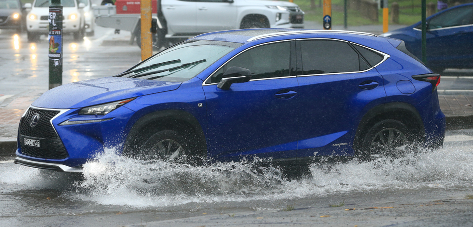SUV drives through deep standing water on roadway
