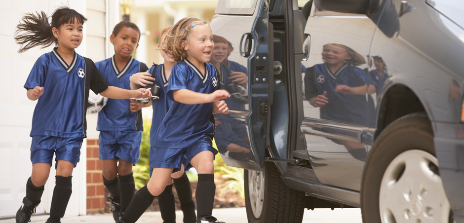 three children in soccer uniforms open door to enter minivan