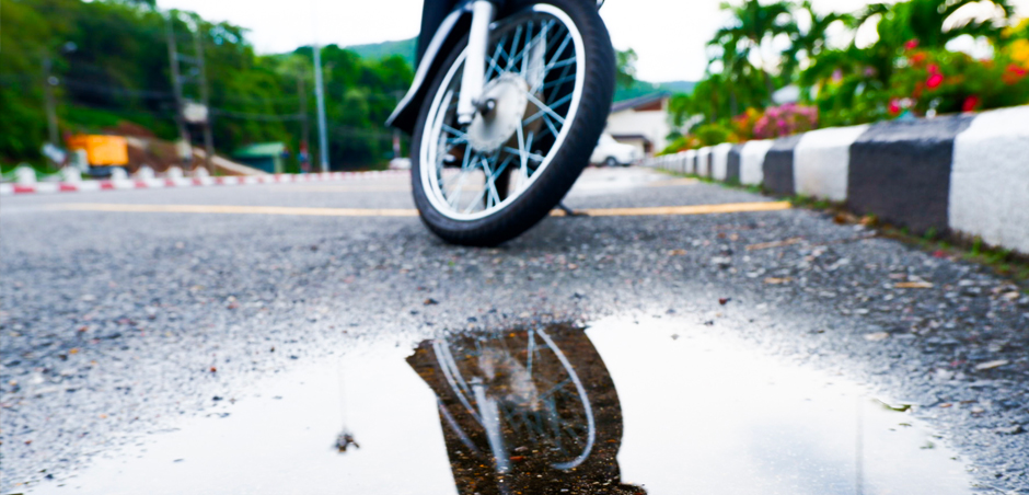 close up of motorcycle front tire in front of puddle on asphalt
