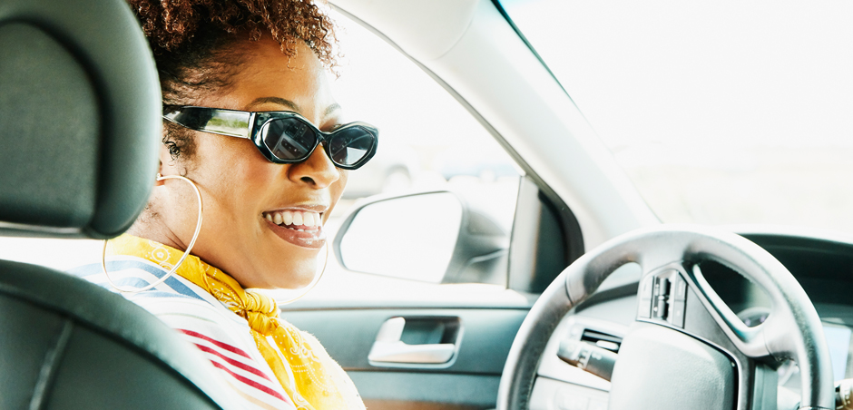woman sits in driver's seat of car and smiles