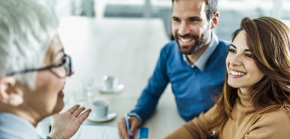 Man and woman meet with silver haired professional at conference table
