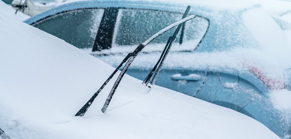 a car, covered in snow, has its windshield wipers pointing up and away from the windshield