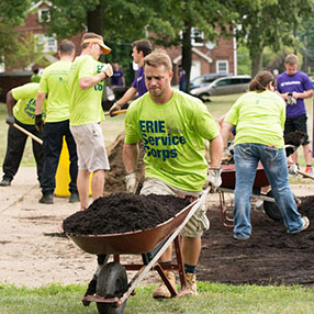 ERIE employee pushing wheelbarrow full of dirt