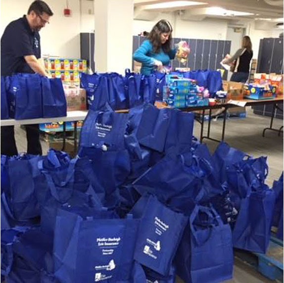 ERIE Employees packing bags with food