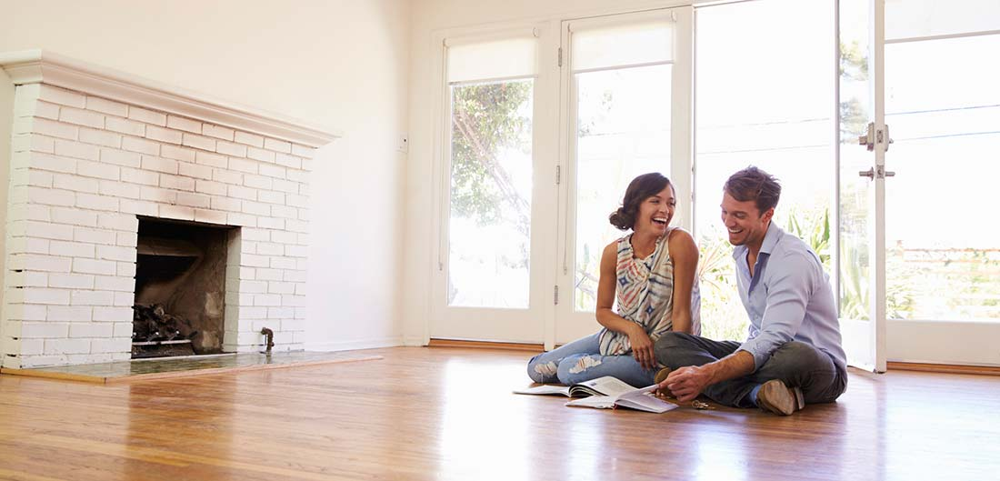 couple sitting on the floor of an empty room