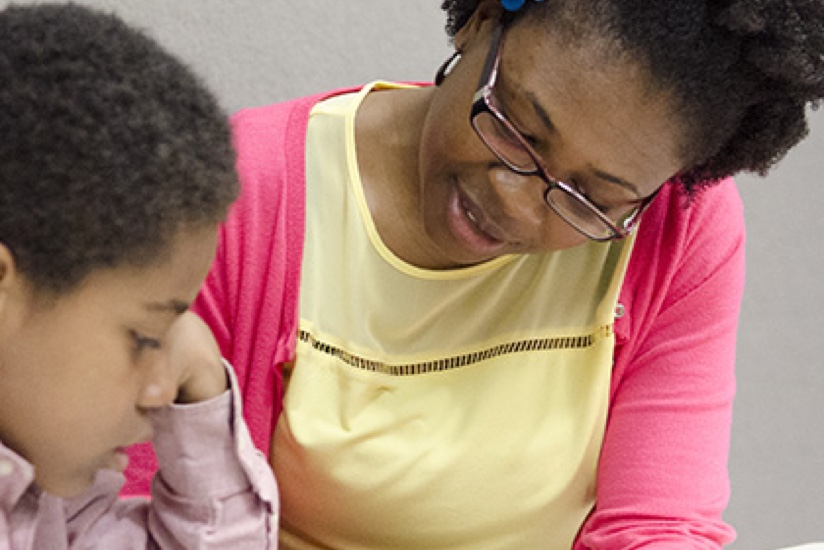 Woman tutoring a child as part of ERIE's Adopt-A-School Partnership with Pfeiffer Burleigh Elementary School